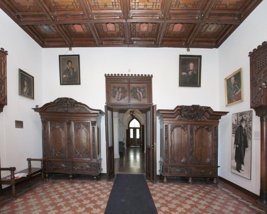 Po wejściu do zamku znajdujemy się w sieni, która podobnie jak inne  wnętrza zamkowe ma XIX-wieczny wystrój wykonany według wzorów wybranych  przez Stoją tu dwie dębowe, bogato rzeźbione szafy gdańskie z początku XVIII w., a na ścianach wiszą portrety z XVIII i XIX w. Do bocznych pomieszczeń wiodą wejścia zdobione portalami w stylu mauretańskim, w lewo do Pokoju Burgrabiego (zarządcy zamku), a w prawo do Pokoju Władysława Zamoyskiego. Szczególną uwagę zwraca drewniany strop z dwoma rzędami kasetonów z  malowanymi herbami przodków Jana Działyńskiego i jego świeżo zaślubionej  w 1858 r. żony Izabelli z Czartoryskich. ówczesnych właścicieli zamku Celinę i Tytusa Działyńskich, a  nawiązujących do sztuki gotyckiej, renesansowej i mauretańskiej Alhambry  (zespół pałaców w Hiszpanii).