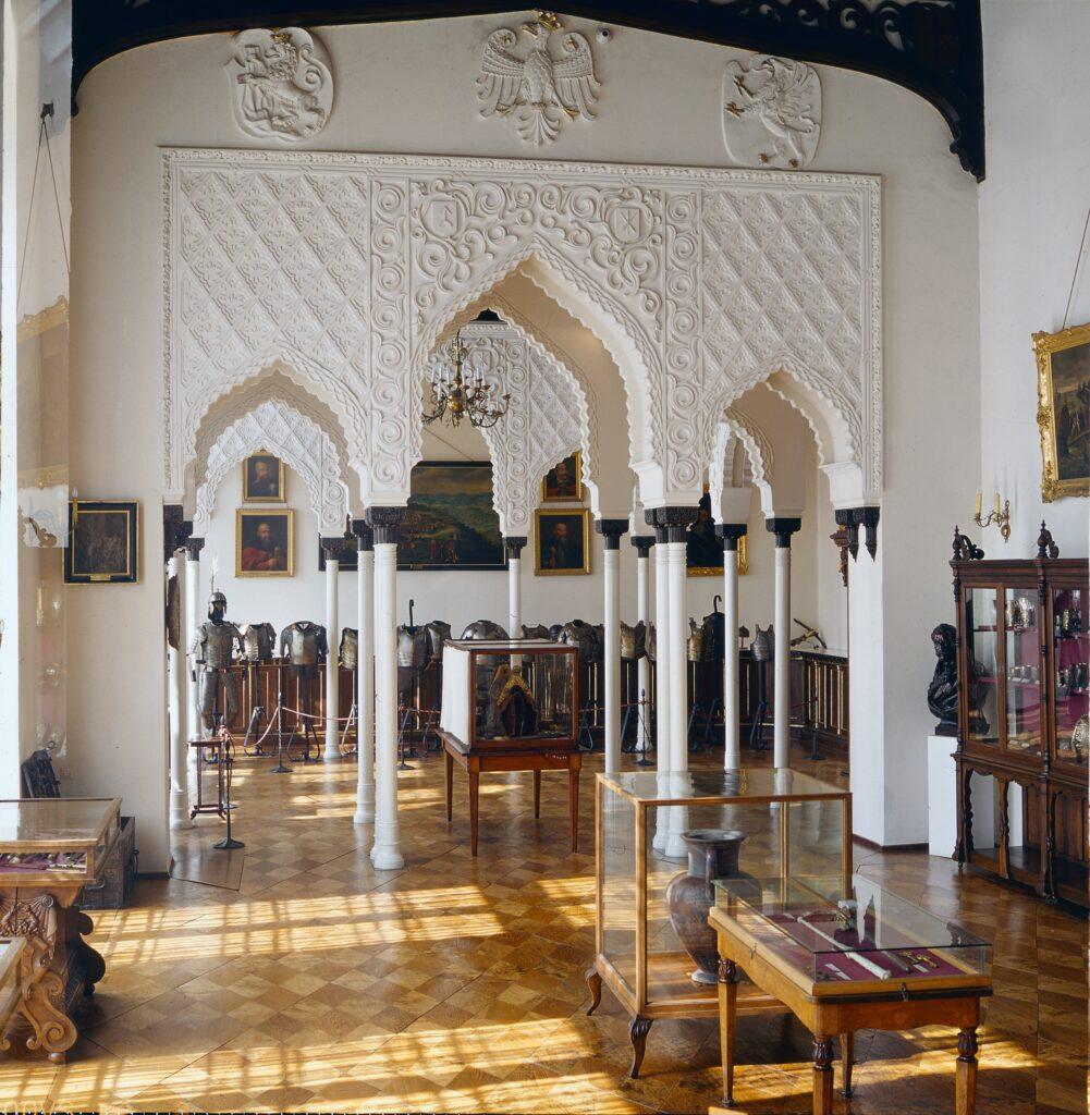 Środkowa część sali jest przykryta płaskim stropem z belkowaniem  sugerującym odkrytą więźbę dachową. Na ścianach umieszczone są wykonane w  sztukaterii herby Polski i Litwy, a także ziem wchodzących niegdyś w  skład Rzeczpospolitej lub lennych w stosunku do niej w XVI w.  W gablotach między oknami wystawiona jest broń pochodzenia wschodniego z XVII i XVIII w. – jatagany i dziryty tureckie oraz buzdygany rotmistrzowskie z ukrytym w trzonie sztyletem. W drugiej gablocie znajdują się paradne karabele z głowniami ze stali damasceńskiej z XVII w.