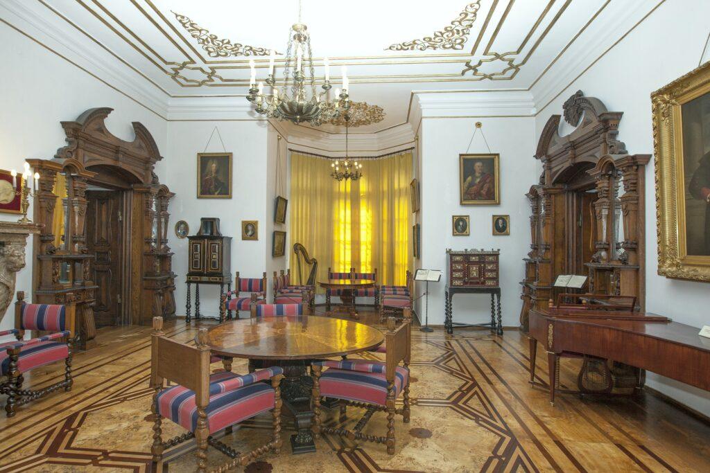Pokój ten  zachował w większości autentyczne urządzenia z połowy XIX w. wykonane  dla tego wnętrza (podobnie jak portale) przez miejscowych – poznańskich i  kórnickich – stolarzy. Są to stojące po bokach wejścia dwie kanapy mahoniowe i dębowe fotele obite pstruchą (wełnianą tkaniną wyrabianą w okolicach Kórnika) oraz pośrodku okrągły stół obrotowy dekorowany mozaiką z sęków 16 gatunków drzew, wg. tradycji pochodzących z kórnickiego parku.