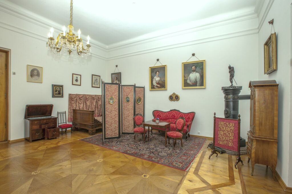 Po lewej stronie znajduje się część pokoju, która pełniła funkcję  sypialni i salonu. Umieszczone są w niej, oddzielone parawanem, XIX  wieczne meble – neobarokowe łoże, szafka nocna i umywalnia. Wiszą tu portrety córek Tytusa Działyńskiego, olejny Cecylii (1836-1896) z 1884 r., akwarela Marii, późniejszej Grudzińskiej i Cecylii w wieku dziecięcym (po 1840 r.) oraz fotografia Anny Potockiej z ok. 1870 r. W ołtarzyku zawieszonym obok łóżka umieszczony jest obraz Chrystusa, szkoły niderlandzkiej z XVII w.  Po drugiej stronie parawanu stoi neobarokowa kanapa z krzesłami i  stołem. Powyżej wiszą portrety, autorstwa lwowskiego malarza Marcina  Jabłońskiego (1801-1876), Wincentyny z Błędowskich Jaźwińskiej z 1851 r., wnuczki Ignacego Działyńskiego, stryja Tytusa oraz jej męża Aleksandra z 1856 r.