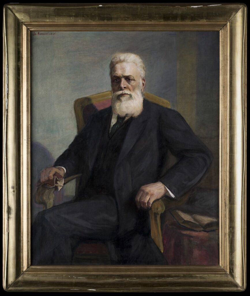 Obraz olejny malowany na płótnie. Na krześle siedzi mężczyzna z nogą założoną na nogę. Mężyczna ma długą siwą brodę, krótko ścięte włosy. Krzesło na złote oparcie, różowe obicie. Obok na stoliczku przykrytym różową tkaniną leży rozłożona książka.