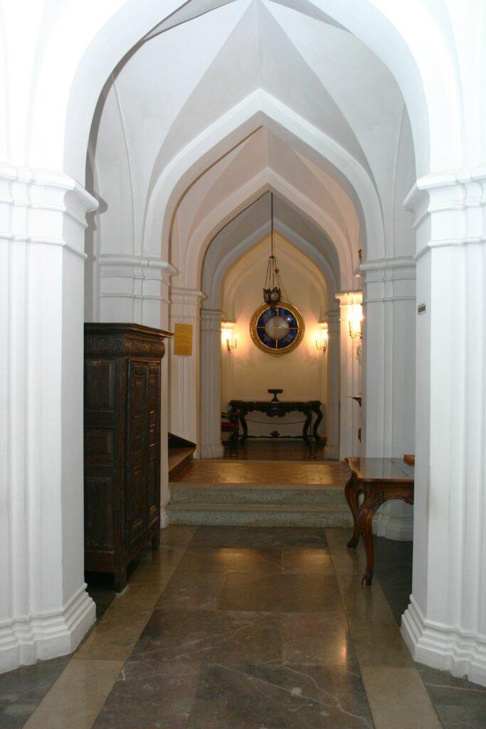 Po wejściu do zamku znajdujemy się w sieni, która podobnie jak inne  wnętrza zamkowe ma XIX-wieczny wystrój wykonany według wzorów wybranych  przez Stoją tu dwie dębowe, bogato rzeźbione szafy gdańskie z początku XVIII w., a na ścianach wiszą portrety z XVIII i XIX w. Do bocznych pomieszczeń wiodą wejścia zdobione portalami w stylu mauretańskim, w lewo do Pokoju Burgrabiego (zarządcy zamku), a w prawo do Pokoju Władysława Zamoyskiego.