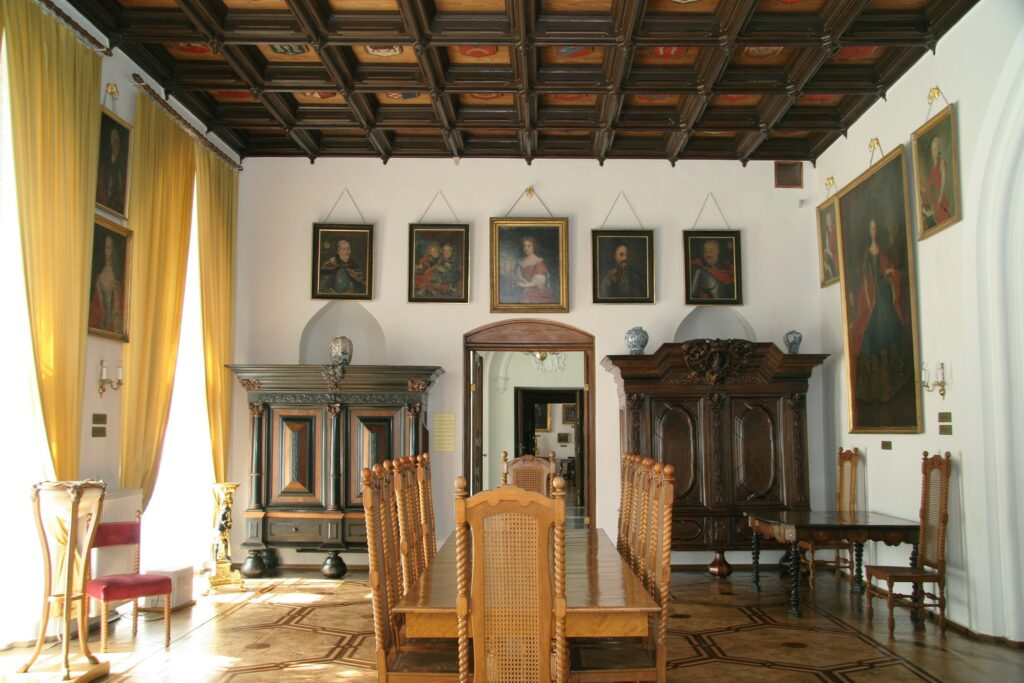 Między oknami zawieszone są portrety ich córek: Doroty Czapskiej (1743-1763), Brygidy Czapskiej (1746-1762) i Nepomuceny Koźmińskiej (1749-1779). Koło szafy gdańskiej umieszczone są podobizny dwóch synów Augustyna: Ksawerego i Ignacego w  wieku dziecięcym z 1759 r. i okresie chłopięcym ok.1765. Z lewej strony  niszy ci sami jako już dorośli mężczyźni są ukazani z żoną starszego z  braci Szczęsną z Woroniczów na obrazie będącym przypuszczalnie dziełem znanego malarza Franciszka Smuglewicza z lat 1791-1793.