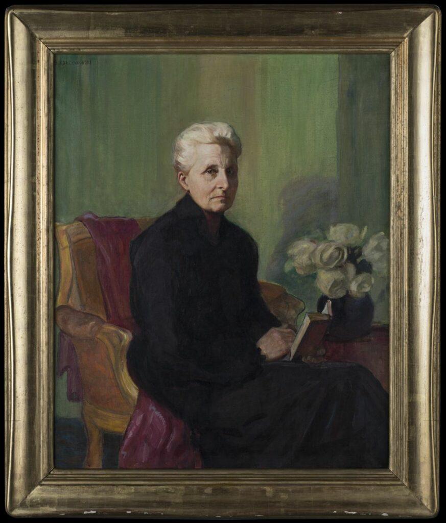 Portret przedstawiający  Marię Zamoyską. Na fotelu z narzuconą kotarą w kolorze czerwonym siedzi kobieta ubrana w czarną suknię. Ma siwe włosy zaczesane do tyłu i spięte w koka. W dłoni trzyma książę. Na stole przykrytym obrusem stoją białe kwiaty w wazonie.