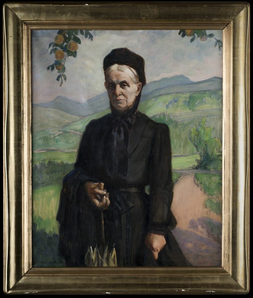 Portret olejny na płótnie przedstawiający kobietę w czarnej sukni, z czepkiem na głowie, z parasolką w ręku i płaszczem przerzuconym na ramieniu. W tle góry oraz drzewo owocowe.