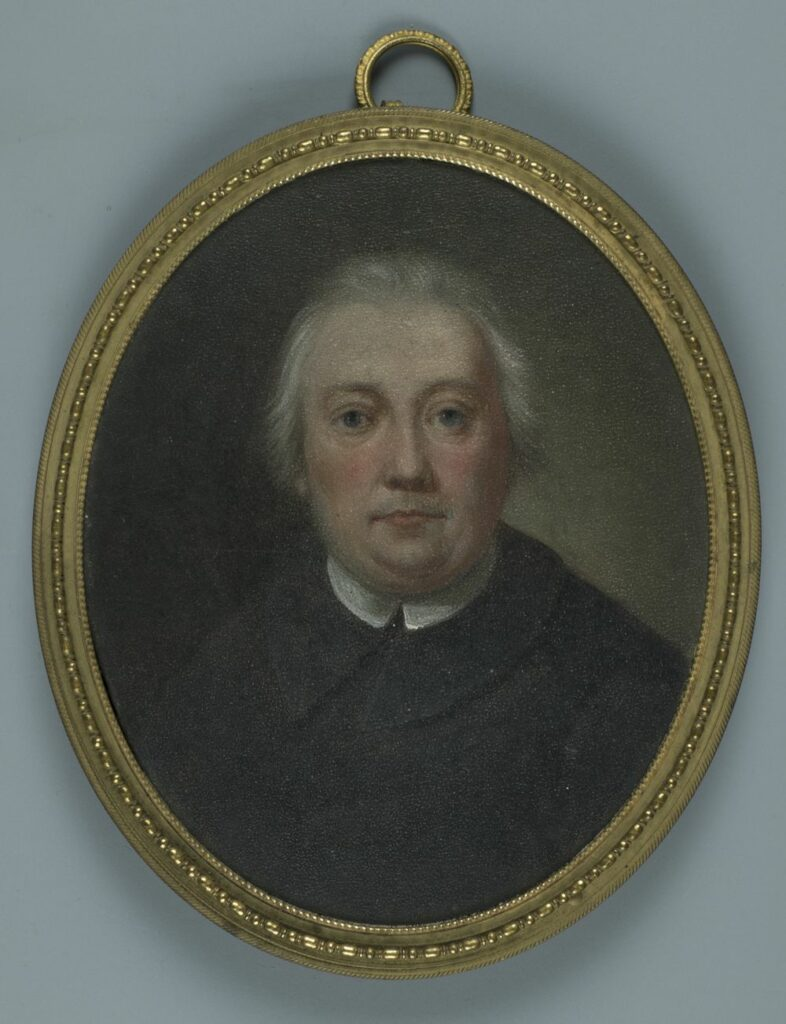 Obraz olejny na desce mahoniowej, w ramce mosiężnej. Portret (popiersie) mężczyzny ukazanego na wprost, w stroju duchownego.
