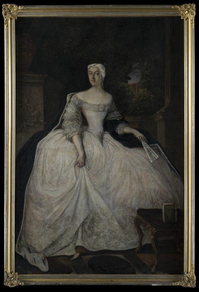 """Pełnopostaciowy portret kobiety w średnim wieku zwróconej twarzą w trzech czwartych w lewo, sylwetką w trzech czwartych w prawo. Kobieta ubrana w białą suknię z wąskim stanikiem zwężającym się klinowo ku dołowi, obszytym srebrną koronką przy półowalnym dekolcie, w klinowym zakończeniu stanika oraz na plisowanych, wielowarstwowych rękawach sięgających połowy przedramienia. Spódnica biała, bardzo szeroka, obszyta u dołu szerokim pasem białej koronki w ornamenty kwiatowe. Z ramion zsunięty ciemnogranatowy, niemal czarny płaszcz podbity futrem sobolowym, obejmujący postać z tyłu, przewieszony przez zagięcie lewego ramienia. Twarz blada, usta wąskie, nos prosty, wydatny, w uszach perłowe kolczyki, na głowie biała peruka zaczesana do tyłu, związana nad karkiem, opadająca na plecy. Na niej na osi srebrny, wzdłużny klejnot. Drugi klejnot w formie stylizowanego kwiatu przypięty nad lewą skronią. Prawa ręka opuszczona wzdłuż ciała, podnosząca lekko skraj spódnicy, ukazująca złotą podszewkę i złoty pantofelek. Lewa ręka odchylona nieco w lewo, trzymająca w dłoni biały wachlarz. Kobieta stoi na posadzce w czerwone romby i czarne koła, wpisane w białe, kwadratowe pola oddzielone czarnymi, prostokątnymi płytkami. Przy prawej krawędzi pola obrazowego barokowy podnóżek na złotych, giętych, rzeźbionych nogach zakończonych kopytami, obity czerwoną tkaniną. Na nim ustawiona pionowo zielona książka ze złotym chrystogramem """"IHS"""" w owalnym polu oraz liliami w narożach. W lewej części pola obrazowego wysoki, szary, prostopadłościenny postument z płaskorzeźbioną postacią putta na ścianie poprzecznej względem osi pola obrazowego, trzymającego owalny, zdobiony wolutami kartusz, zwieńczony otwartą koroną, w którego dwudzielnym polu godła herbów Ogończyk i Topór. Powyżej profilowany gzyms. Na postumencie ustawiona złota waza z girlandami na brzuścu oraz stylizowanymi liśćmi akantu. W prawej krawędzi pola obrazowego za kobietą fragment kamiennej balustrady z profilowanym gzymsem dochodzącej do """