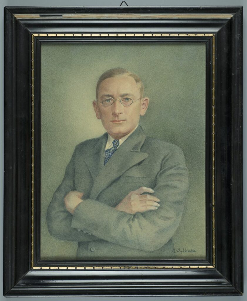 Półpostaciowy portret młodego mężczyzny zwróconego twarzą i sylwetką w trzech czwartych w lewo. Mężczyzna ubrany w szarą, jednorzędową marynarkę z szerokimi klapami, pod którą widoczna biała koszula z kołnierzykiem oraz błękitny krawat w czarne wzory. Włosy zaczesane na bok, z przedziałkiem po lewej stronie, w kolorze jasny blond. Twarz rumiana, oczy niebieskie, na nosi druciane, owalne okulary. Ręce mężczyzny skrzyżowane na piersi. Tło przedstawienia szare, jaśniejsze przy głowie postaci.